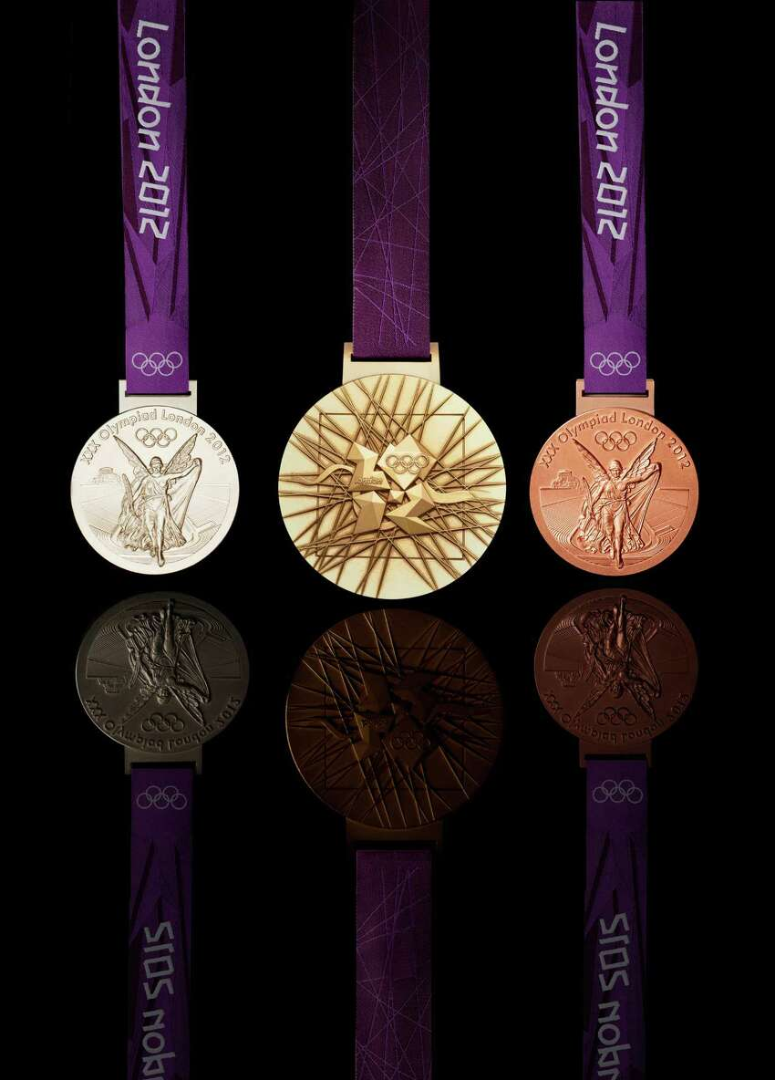 In this image made available by the London Organising Committee of the Olympic Games on Wednesday, July 27, 2011, show the London 2012 Olympic medals designed by British artist David Watkins. The front of the silver medal is at left, the back of the gold medal at center and the front of the bronze medal is at right. All medals will be 3.35 inches (85 mm) in diameter.