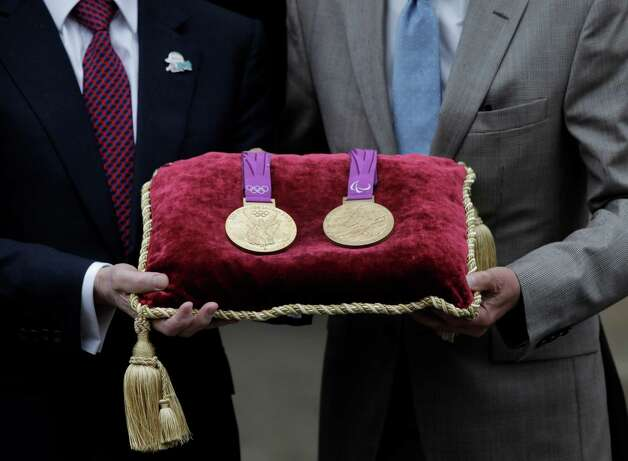 Sebastian Coe (right), chairman of the London 2012 Organizing Committee, and Jan du Plessis (left), Rio Tinto mining company chairman, pose for the photographers holding a gold medal of the Games, at the Tower of London, in London, Monday, July 2, 2012. The company is responsible for the production of the precious metals for the London 2012 Games, and has handed over the final Olympic and Paralympic medals to LOCOG for secure storage in the vaults at the Tower of London during the Games. The gold, silver and bronze medals which will be awarded to the athletes at Games-times, will remain there until they are needed for the Victory Ceremonies. In total, 4,700 medals have been produced and will be awarded in 805 Victory Ceremonies that will take place in over 30 London 2012 venues across the UK. Photo: Lefteris Pitarakis, Associated Press