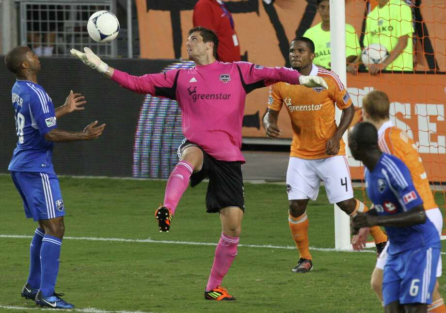 Dynamo goalkeeper Tally Hall saves the ball against the Montreal Impact during the first half. Photo: J. Patric Schneider, For The Chronicle / Houston Chronicle