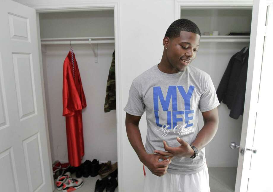 Courtney Williams lived at the Star of Hope Mission during high school and once feared he wouldn't graduate. The gown in his closet is proof that he did. Now he has a full scholarship to the University of Houston. Photo: Melissa Phillip / © 2012 Houston Chronicle