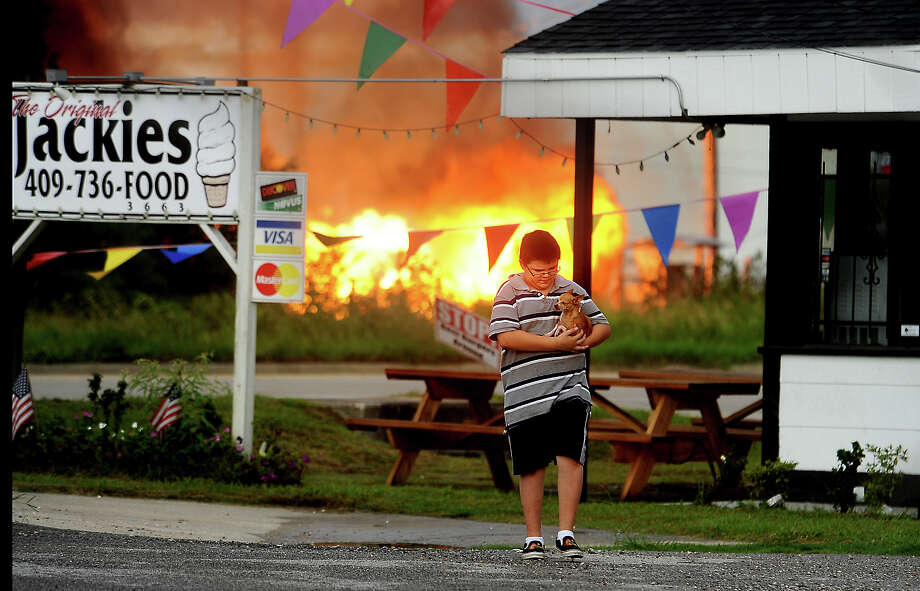 Brandon Oranday walks down 60th Street after retrieving a neighbor's dog as a pipeline fire blazes in the background in Port Arthur, Saturday, July 21, 2012. Tammy McKinley/The Enterprise Photo: TAMMY MCKINLEY