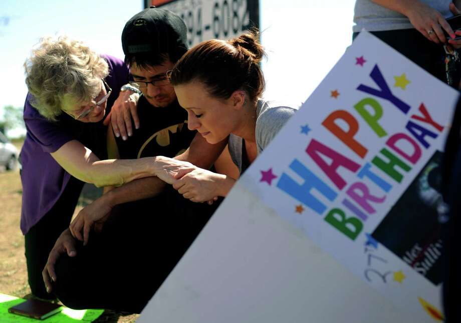From left, Pastor Mary Lu Saddoris comforts Isaac Pacheco and Courtney McGregor, friends of shooting  victim Alex Sullivan, on Saturday at a memorial near the movie theater in Aurora, Colo. Photo: Hyoung Chang / The Denver Post