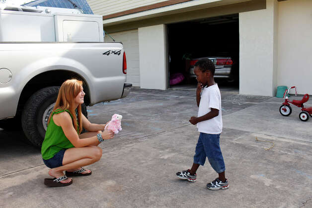 Katy Hagerup gives John Kulimushi, 4, a gift of a stuffed lamb upon her arrival at the home of her in-laws, Scott and Nancy Hagerup, on Saturday, July 21, 2012. Kulimushi and his family are living with the Hagerups since being evicted from their San Antonio apartment Tuesday. Photo: Lisa Krantz, San Antonio Express-News / San Antonio Express-News