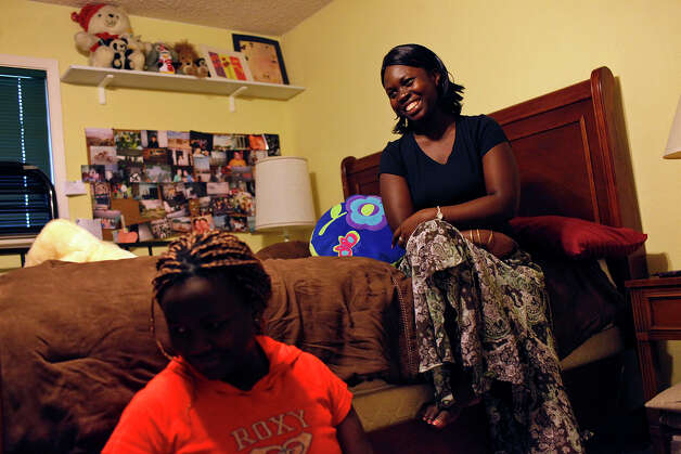 Faida Lambere, 17, and her sister, Kito Feza, 13, sit in their new bedroom on Saturday, July 21, 2012, at the home of Scott and Nancy Hagerup, where they are living since being evicted from their San Antonio apartment Tuesday. Photo: Lisa Krantz, San Antonio Express-News / San Antonio Express-News