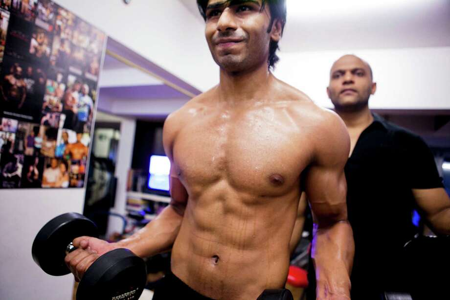 Satyajit Chaurasia, right, trains a Bollywood actor at a gym in Mumbai, India. Since the 1990s, there has been a growing number of well-muscled leading men. Photo: PRASHANTH VISHWANATHAN / NYTNS