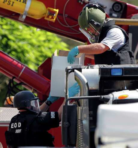 Explosives from the Colorado apartment of alleged gunman James Holmes are loaded with sand into a dump truck for disposal on Saturday. Photo: Alex Brandon / AP