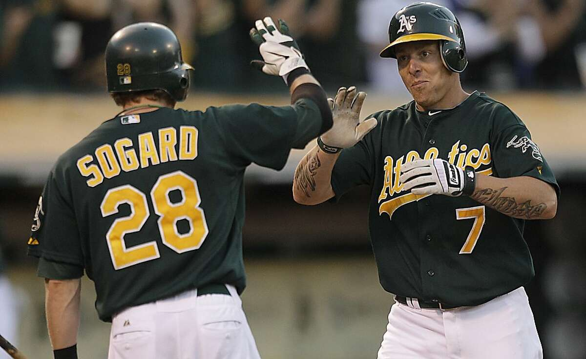 Oakland Athletics' Brandon Inge, right, celebrates with teammate Eric Sogard (28) after hitting a home run off New York Yankees' Phil Hughes in the eighth inning of a baseball game on Saturday, July 21, 2012, in Oakland, Calif. (AP Photo/Ben Margot)