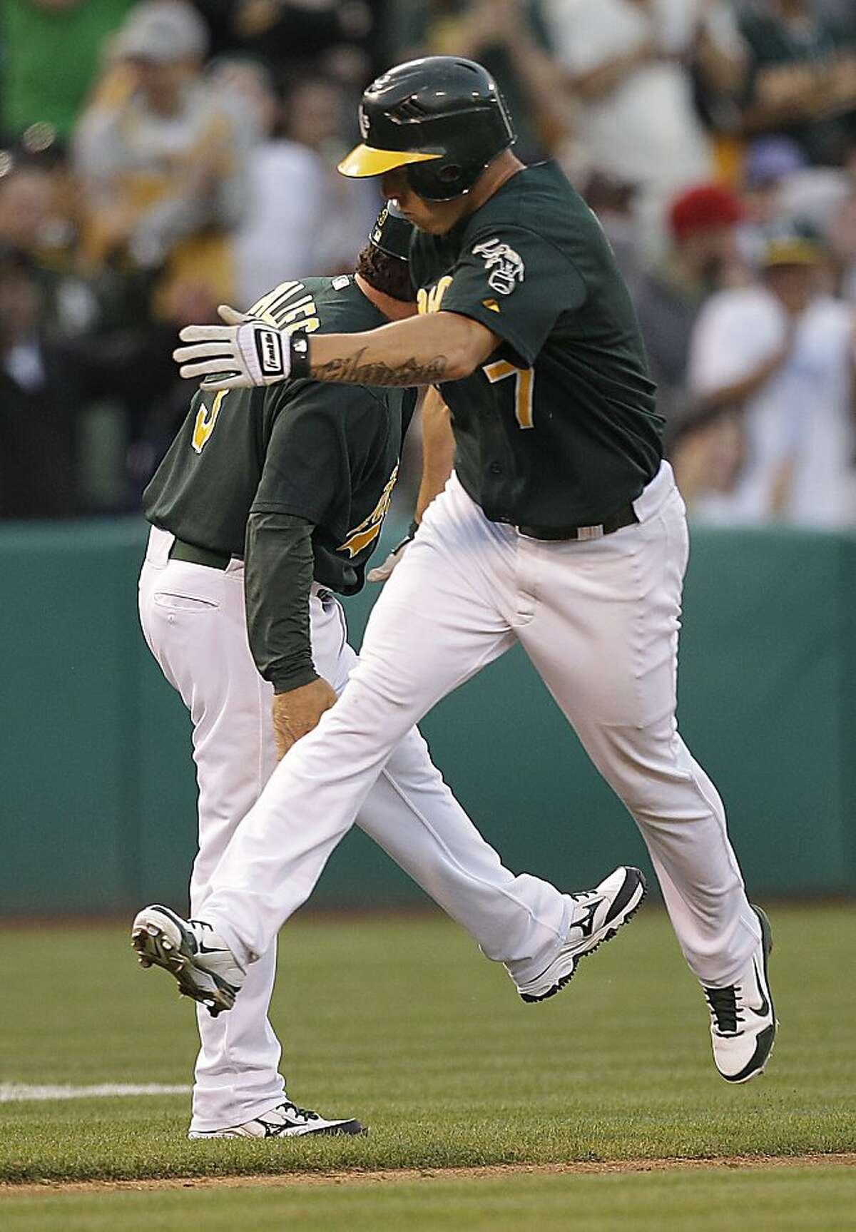 Oakland Athletics' Brandon Inge, right, celebrates with third base coach Mike Gallego after hitting a home run off New York Yankees' Phil Hughes in the eighth inning of a baseball game on Saturday, July 21, 2012, in Oakland, Calif. (AP Photo/Ben Margot)
