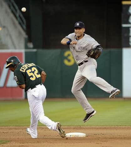 OAKLAND, CA - JULY 21: Derek Jeter #2 of the New York Yankees gets his throw off to complete the double-play while avoiding Yoenis Cespedes #52 of the Oakland Athletics in the seventh inning at O.co Coliseum on July 21, 2012 in Oakland, California. The Athletics won the game 2-1. (Photo by Thearon W. Henderson/Getty Images) Photo: Thearon W. Henderson, Getty Images
