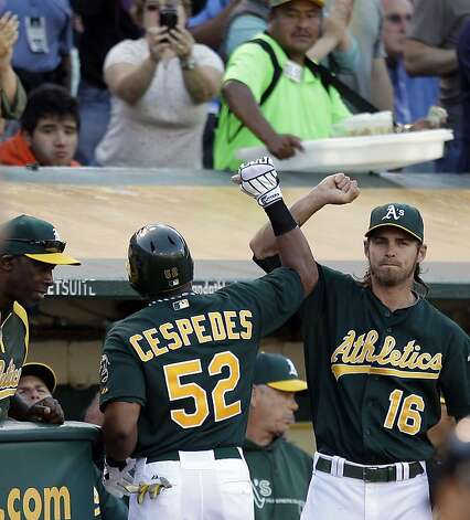 Oakland Athletics' Yoenis Cespedes (52) is congratulated by teammate Josh Reddick (16) after hitting a home run off New York Yankees' Phil Hughes in the fourth inning of a baseball game on Saturday, July 21, 2012, in Oakland, Calif. (AP Photo/Ben Margot) Photo: Ben Margot, Associated Press