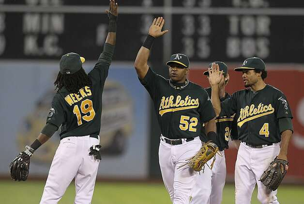 From left, Oakland Athletics Jemile Weeks (19), Yoenis Cespedes (52) and Coco Crisp celebrate the 2-1 victory over the New York Yankees after a baseball game Saturday, July 21, 2012, in Oakland, Calif. (AP Photo/Ben Margot) Photo: Ben Margot, Associated Press