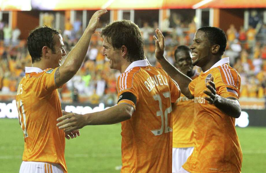 Dynamo defender Bobby Boswell, center, headed in Brad Davis' corner kick in the 84th minute for the second Dynamo goal against the Impact. Davis, left, entered the match in the 68th minute. Photo: J. Patric Schneider / Houston Chronicle