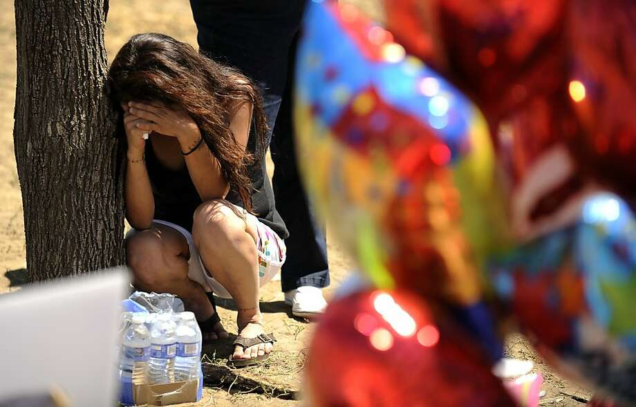 """A woman grieves by the memorial for the shooting victims, Saturday, July 21, 2012 in Aurora, Colo. Twelve people were killed and dozens were injured in the attack early Friday, July 20, 2012 at the packed theater during a showing of the movie, """"The Dark Knight Rises."""" in Aurora, Colo.   Police have identified the suspected shooter as James Holmes, 24. (AP Photo/The Denver Post, Hyoung Chang) TV, INTERNET AND MAGAZINES CALL FOR RATES AND TERMS Photo: Hyoung Chang, Associated Press"""