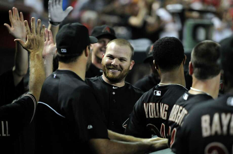 Arizona's Jason Kubel work his way through the high-five line yet again after hitting his third home run of the game in the sixth inning on Saturday. Photo: Norm Hall / 2012 Getty Images
