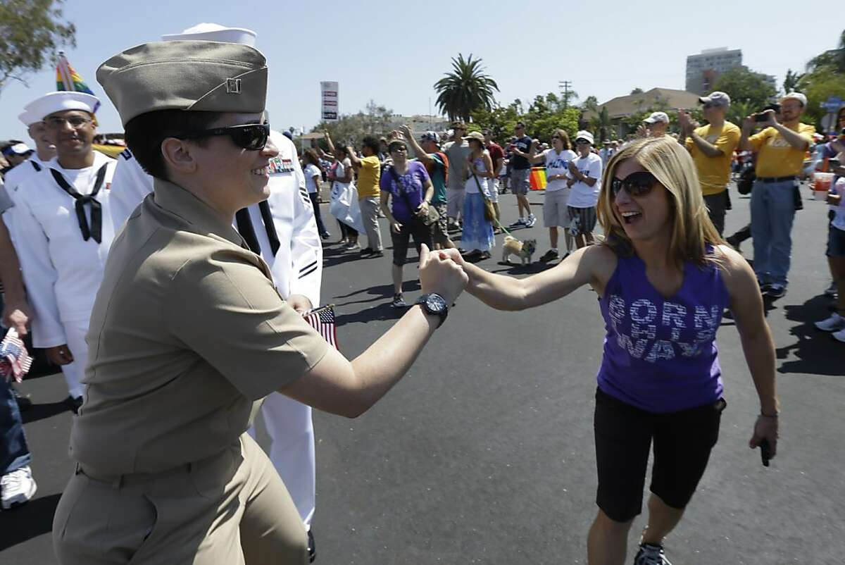 RETRANSMISSION TO CORRECT RANK - Navy Lt. Perry, left, greets a woman during the gay pride parade Saturday, July 21, 2012, in San Diego. For the first time ever, U.S. service members marched in a gaypride event decked out in uniform Saturday, after a recent memorandum from the Defense Department to all military branches made an allowance for the San Diego parade - even though its policy generally bars troops from marching in uniform in parades. (AP Photo/Gregory Bull)
