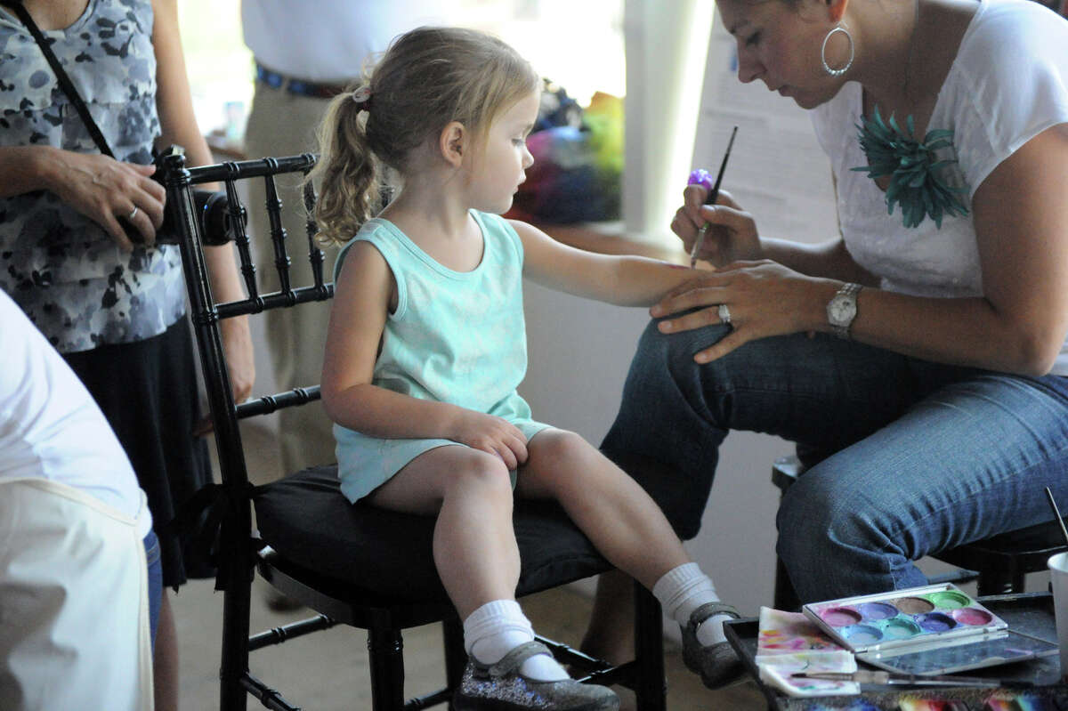 Mari Pritchard, 3, watches Holly Lapine paint on her arm during the DSSD's Roll'n on the River benefit for the Mill River Park at 1010 Washington Boulevard in Stamford, Conn., July 22, 2012. The event features live animals, crafts and music.