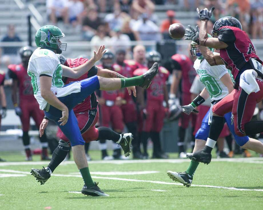The Militia's Desmond Miller blocks a Hartford Whalers punt during Western Connecticut's NEFL season opener Sunday at Immaculate High School. Photo: Barry Horn / The News-Times Freelance