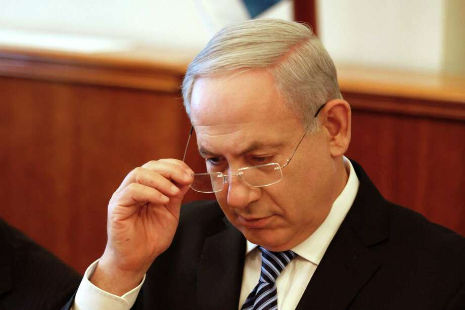 Israeli Prime Minister Benjamin Netanyahu opens the weekly cabinet meeting at his office in Jerusalem, Sunday, July 22, 2012. The Israeli government is asking the country?s Supreme Court to delay the evacuation of an unauthorized West Bank settlement outpost by a month. The court has ordered the Migron outpost dismantled by Aug. 1, 2012. (AP Photo/Gali Tbbon, Pool) Photo: Gali Tibbon / AFP POOL