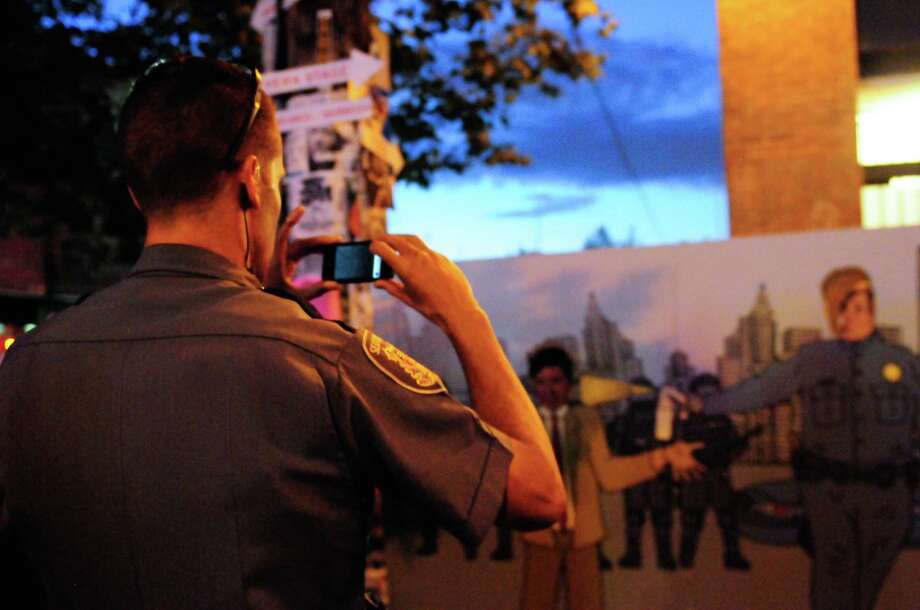 A Seattle Police officer helps take a picture of two attendees in a Seattle version of the  pepper-spray cop meme. Photo: LINDSEY WASSON / SEATTLEPI.COM