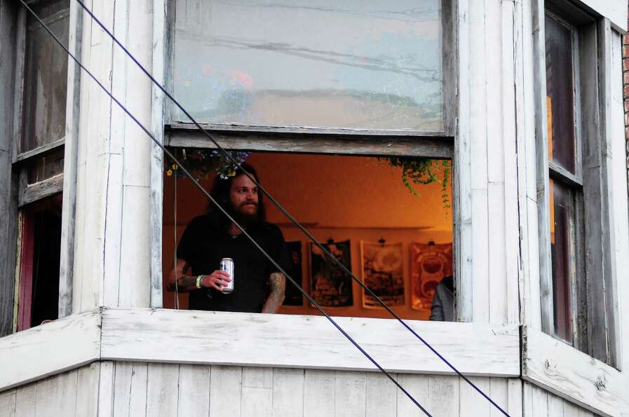 A man looks out at the crowd with a beer in hand from a nearby apartment.