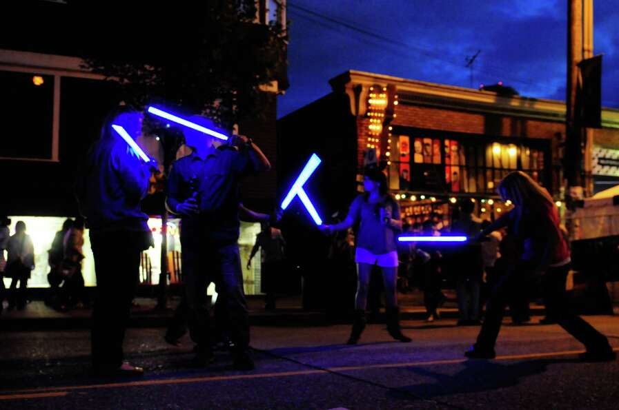 Partygoers play with light sabers.
