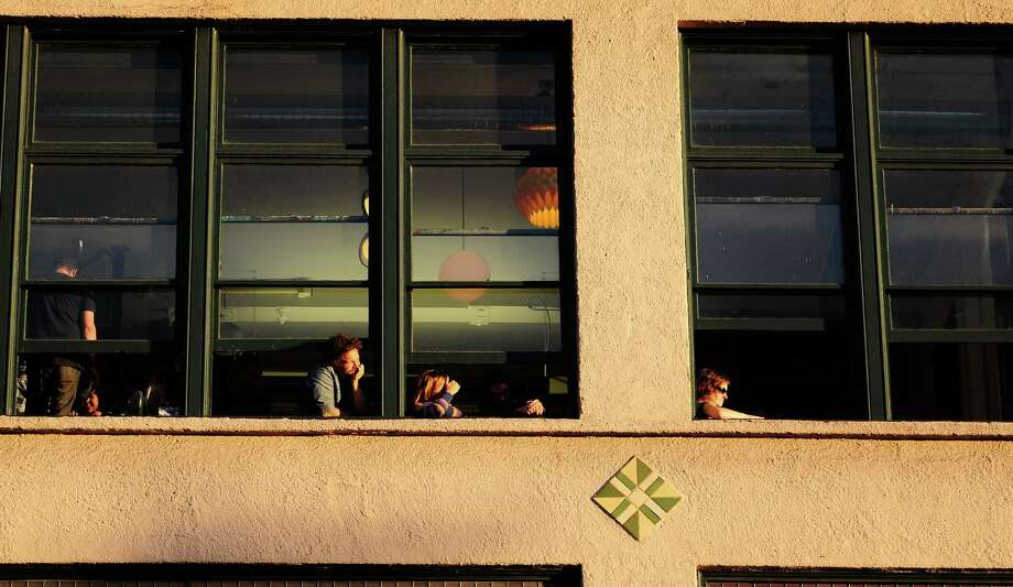 People watch the mainstage from a nearby building as the sun sets. Photo: LINDSEY WASSON / SEATTLEPI.COM