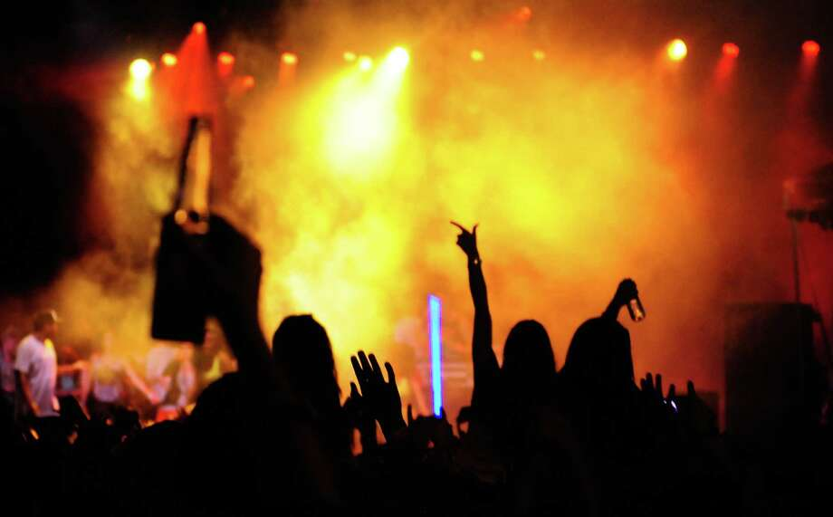 People are silhouetted against the colorful lights of Major Lazer's performance. Photo: LINDSEY WASSON / SEATTLEPI.COM