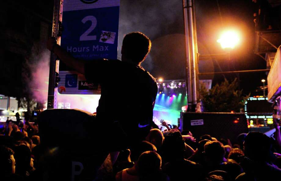 One spectator sits on a parking meter to grab a better view of Major Lazer's performance. Photo: LINDSEY WASSON / SEATTLEPI.COM