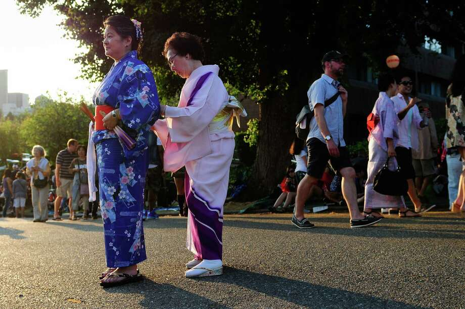 Rose Kishi, right, helps Karen Yoshitomi with her obi, or sash, before a dance  at the 80th annual Bon Odori celebration outside the Seattle Buddhist Temple on Saturday, July 21, 2012. Bon Odori, or Obon, is a traditional Japanese festival featuring music and line dancing to celebrate the lives of ancestors. Photo: LINDSEY WASSON / SEATTLEPI.COM
