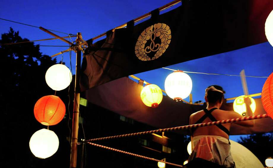 A taiko drummer is lit by traditional lanterns. Photo: LINDSEY WASSON / SEATTLEPI.COM