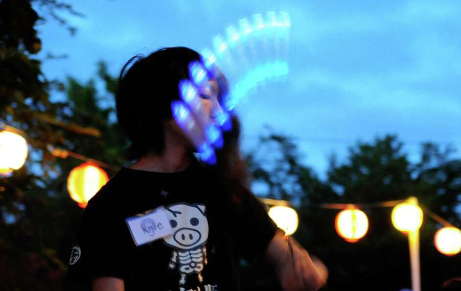 Kyle Woo does some poi spinning with blue lights during a break.