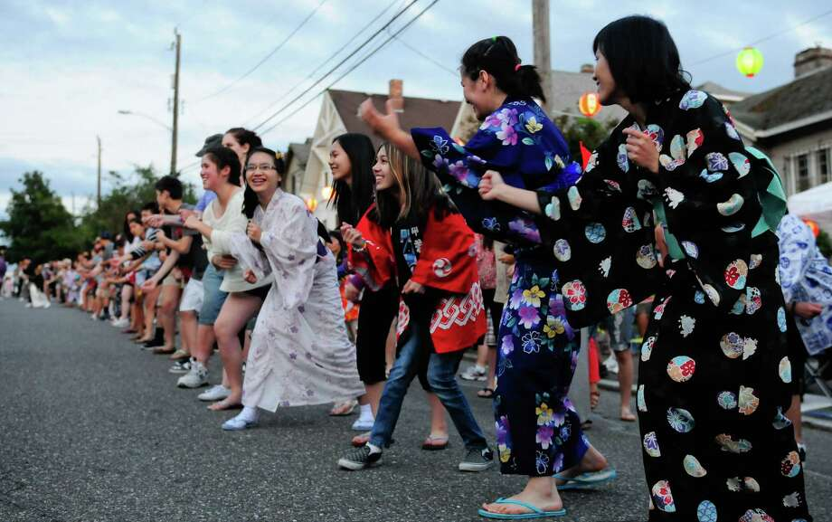 People pretend to cast fishing nets as they perform Soran Bushi, the fisherman's dance. Photo: LINDSEY WASSON / SEATTLEPI.COM