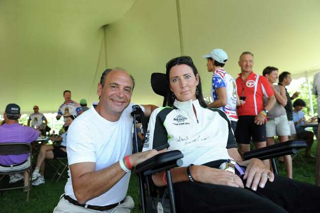 Denis Rizzuto of Greenwich, and his wife, Christie, who had ALS, at the end of the ALS TDI Tri-State Trek in Greenwich, Sunday, July 22, 2012. The three-day, 270-mile bicycle ride began in Newton, Mass., Friday and ended in Greenwich Sunday afternoon, and raises money for ALS research. Photo: Helen Neafsey / Greenwich Time