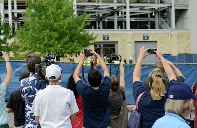 Spectators watch and photograph the removal of the statue of former Penn State football coach Joe Paterno Sunday, July 22, 2012 in State College, Pa. The famed statue was taken down from outside the Penn State football stadium Sunday, eliminating a key piece of the iconography surrounding the once-sainted football coach accused of burying child sex abuse allegations against a retired assistant. (AP Photo/John Beale) Photo: John Beale