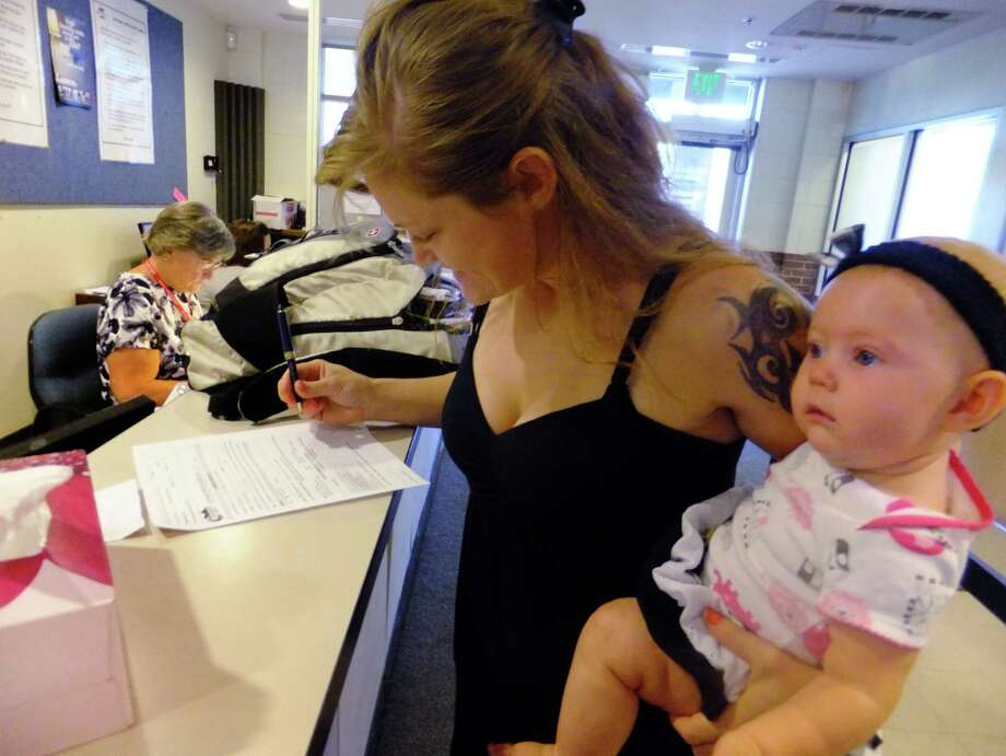 In this July 16, 2012, photo, Laura Fritz, 27, left, with her daughter Adalade Goudeseune fills out a form at the Jefferson Action Center, an assistance center in the Denver suburb of Lakewood. Both Fritz grew up in the Denver suburbs a solidly middle class family, but she and her boyfriend, who has struggled to find work, and are now relying on government assistance to cover food and $650 rent for their family. The ranks of America's poor are on track to climb to levels unseen in nearly half a century, erasing gains from the war on poverty in the 1960s amid a weak economy and fraying government safety net. Census figures for 2011 will be released this fall in the critical weeks ahead of the November elections. (AP Photo/Kristen Wyatt) Photo: Kristen Wyatt / AP