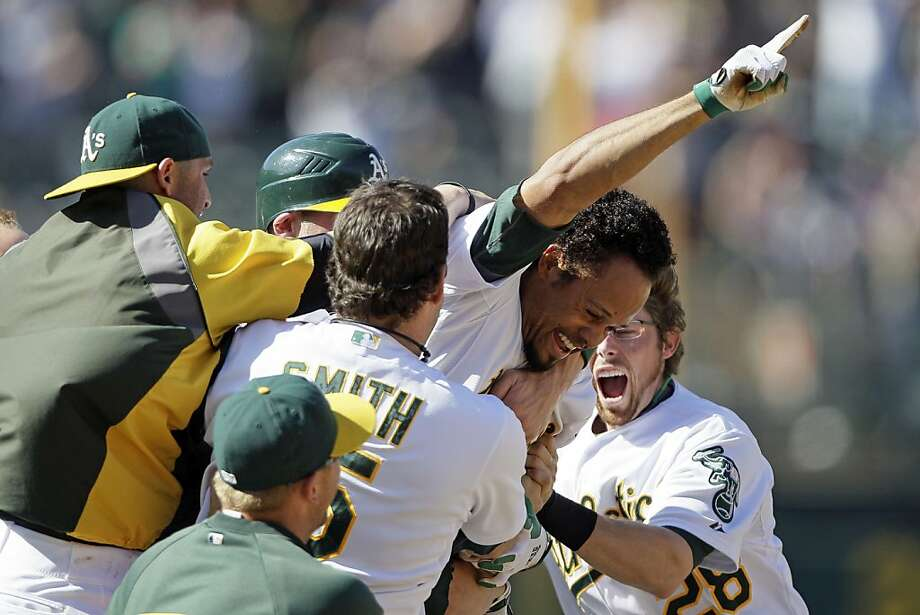 Oakland Athletics' Coco Crisp, center, is mobbed by teammates after driving in the winning run in the 12th inning of their baseball game against the New York Yankees, Sunday, July 22, 2012, in Oakland, Calif. Oakland won 5-4. (AP Photo/Eric Risberg) Photo: Eric Risberg, Associated Press