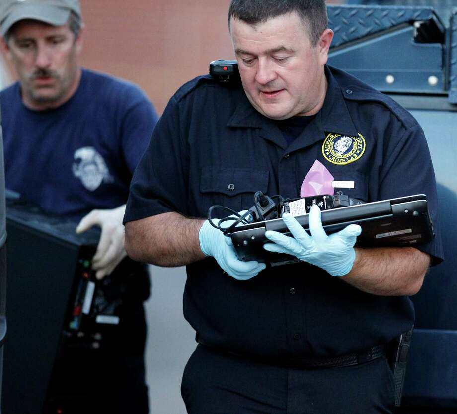 Investigators in Aurora, Colo., remove computer equipment Saturday linked to alleged gunman James Holmes. Authorities say it is nearly impossible to stop shooting sprees. Photo: Alex Brandon / AP