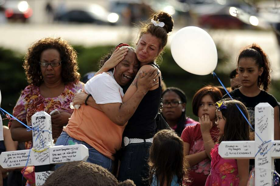 "People comfort each other at the memorial for the Century 16 movie theater shooting victims in Aurora, Colo. Sunday, July 22, 2012. 12 cross are placed at the Memorial. 12 people were killed and 58 were injured in a shooting during an early Friday premiere of ""The Dark Knight Rises."" (AP Photo/The Denver Post, Hyoung Chang) TV, INTERNET AND MAGAZINES CALL FOR RATES AND TERMS Photo: Hyoung Chang, Associated Press"