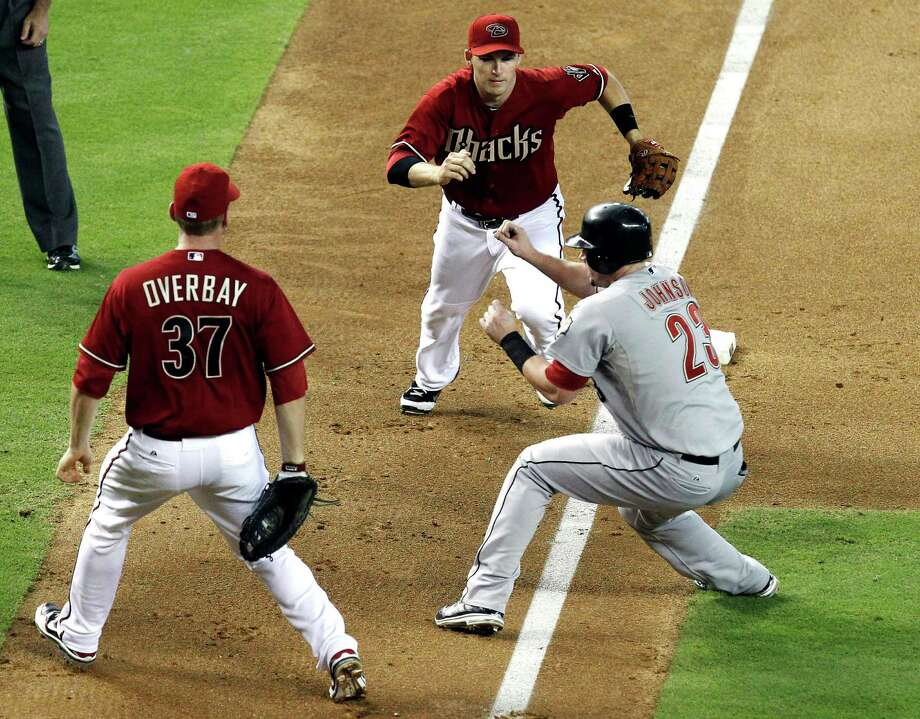 Chris Johnson (23) gets caught in a rundown on a botched squeeze play in the sixth, just before the Diamondbacks took control with a seven-run inning. Photo: Ross D. Franklin / AP