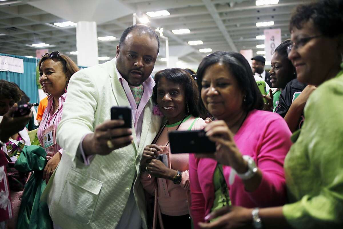 Roland Martin, of CNN, poses with fans at the AKA sorority convention at Moscone Convention Center in San Francisco, Calif. on Sunday, July 22, 2012.