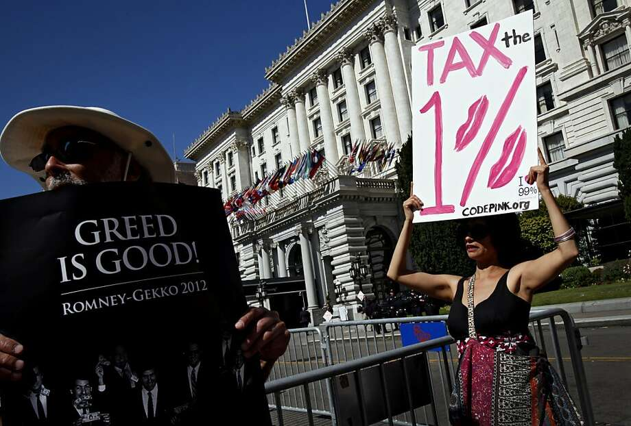 Nancy Mancias, right, of San Rafael, and Barry Lefsky, left, of Oakland, protest the visit of GOP presidential candidate Mitt Romney at the Fairmont Hotel in San Francisco, Calif., Sunday, July 22, 2012. Photo: Sarah Rice, Special To The Chronicle