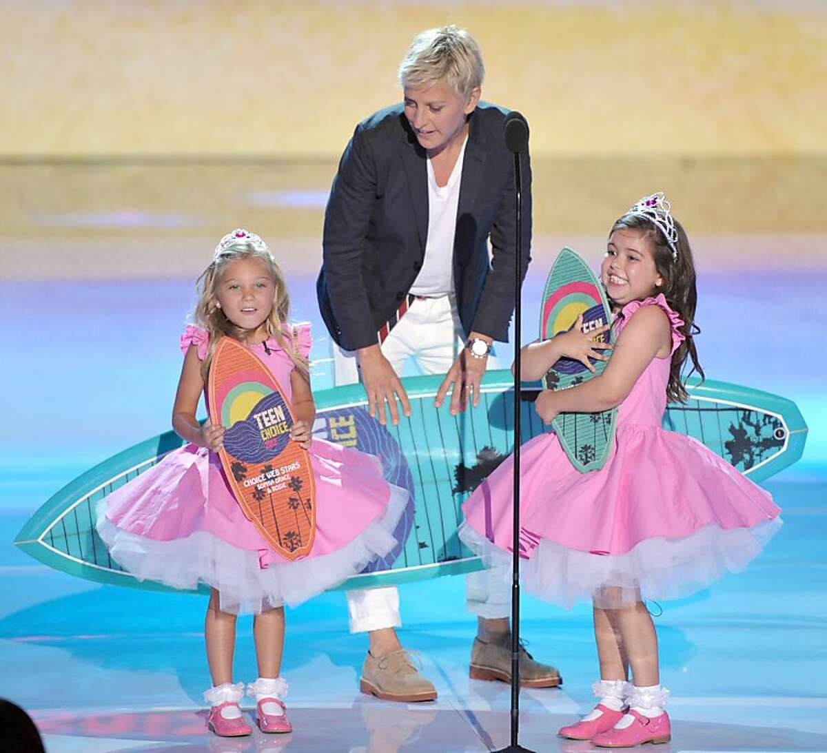 Ellen DeGeneres, center, accepts the award for choice comedian onstage with Rosie Mcclelland, left, and Sophia Grace Brownlee at the Teen Choice Awards on Sunday, July 22, 2012, in Universal City, Calif. (Photo by John Shearer/Invision/AP)