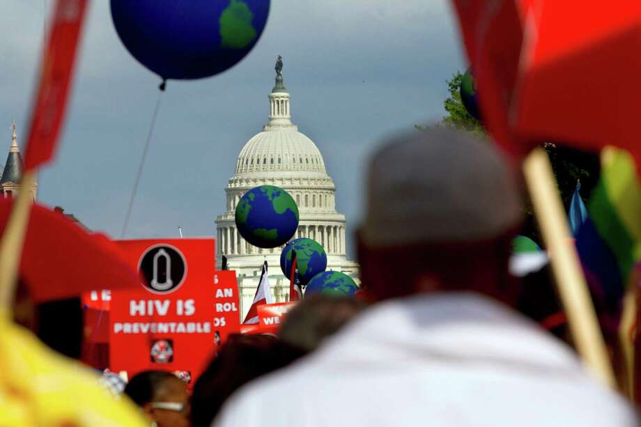 People hold signs and balloons as they participate in the AIDS March in Washington, Sunday, July 22, 2012. (AP Photo/Jacquelyn Martin) Photo: Jacquelyn Martin / AP