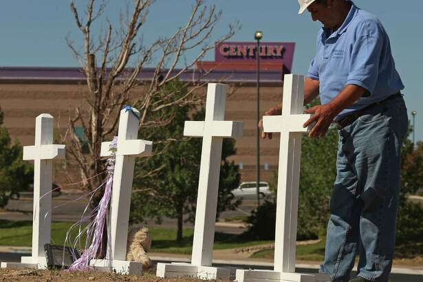 AURORA, CO - JULY 22: Greg Zanis of Aurora, Illinois, places two of the twelve crosses he made for a makeshift memorial to the victims of last weekend's mass shooting at the Century 16 movie theater (background) July 22, 2012 in Aurora, Colorado. A carpenter by trade, Zanis made the twelve white crosses that were placed near Columbine High School after a mass shooting there in 1999. Zanis said he made these crosses as fast as possible and drove all night across the country to place them across the street from the theater. Police in Aurora, a suburb of Denver, say they have James Holmes, 24, in custody after he killed 12 people and injured 59 during a midnight screening of 'The Dark Knight Rises' last Friday. (Photo by Chip Somodevilla/Getty Images)