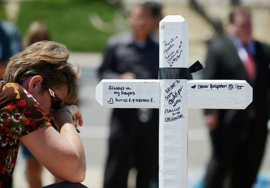 Angie Terry of Alabama prays next to a cross erected after Friday's theater massacre in Aurora, Colo.  Greg Zanis, the Aurora, Ill., man who put up crosses after the 1999 Columbine High School massacre, was back in Colorado to do the same in memory of the latest victims. Photo: Kevork Djansezian / 2012 Getty Images