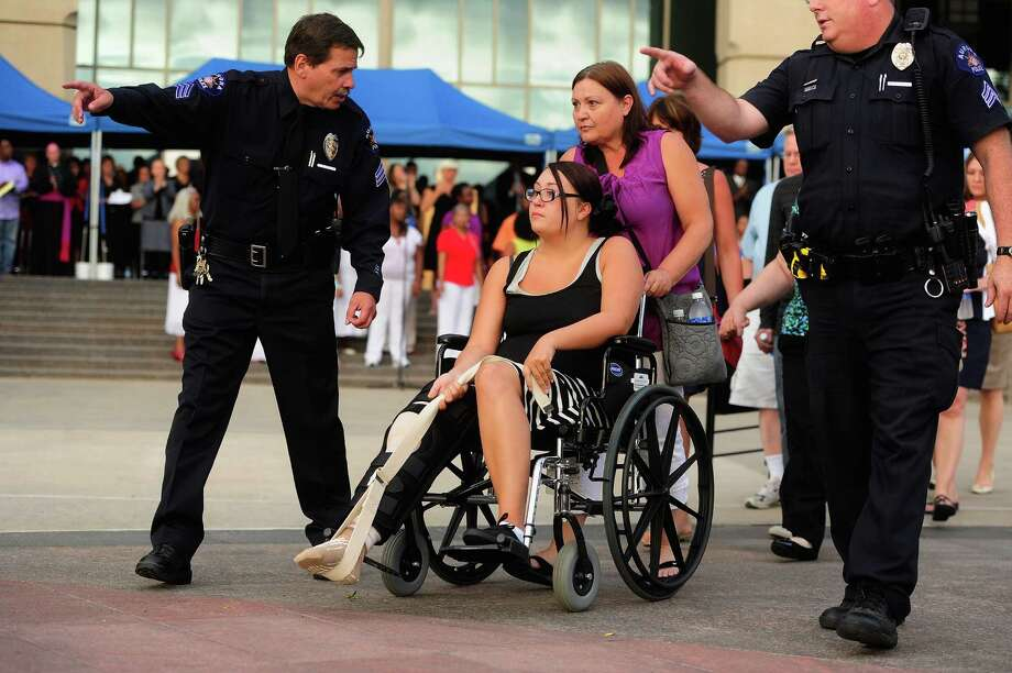 A victim of the mass shooting at the Century 16 movie theater is escorted by police officers Sunday during a prayer vigil at the Aurora Municipal Center in Aurora, Colo. Photo: Pool / 2012 Getty Images