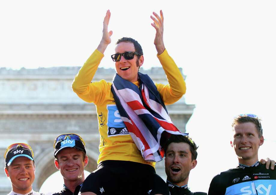 Bradley Wiggins gets the royal treatment from his teammates after his Tour de France victory Sunday. Photo: Bryn Lennon / 2012 Getty Images