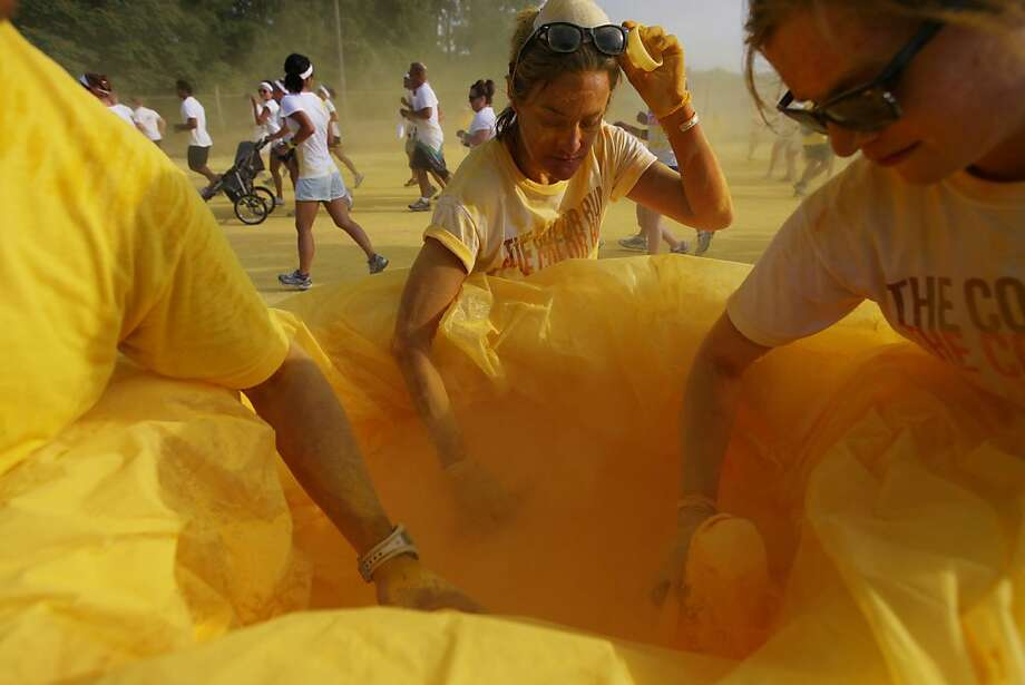 Lynn Chamberlain, 54, of Ann Arbor, Mich.,center scoops up yellow powder with her daughter Fiona Nowlin, 24, of Ann Arbor, as they volunteer on behalf of the Food Gatherers as runners are literally powdered down in a variety of colors as they participate in the The Color Run 5k in Ypsilanti, Mich.,  Sunday, July 22, 2012. (AP Photo/Detroit Free Press, Mandi Wright) Photo: Mandi Wright, Associated Press