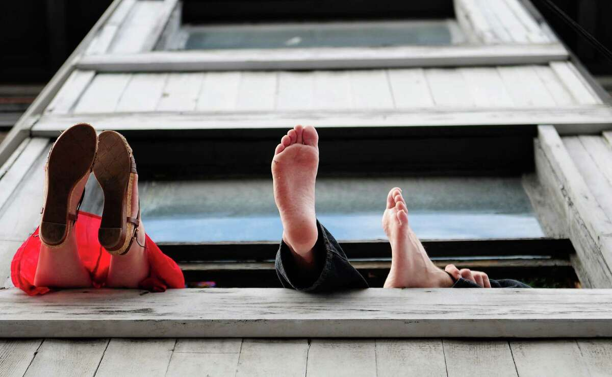 Some spectators let their feet dangle out of an apartment over Ballet Vietnamese restaurant on 10th and East Pike.