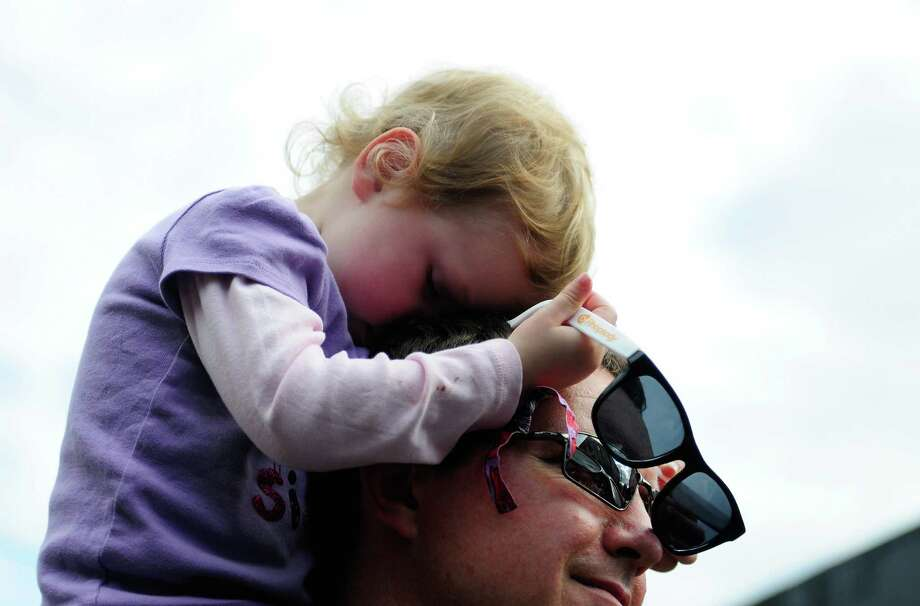 Molly Venard, 3, is a bit tired from all the excitement as she rests on the shoulders of her father, Jacob. Photo: LINDSEY WASSON / SEATTLEPI.COM